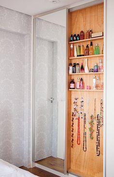 O espaço entre um pilar e o banheiro deu origem ao armário, com 15 cm de profundidade. Os perfumes ficam em prateleiras e, abaixo delas, ganchos seguram colares. Projeto da arquiteta Tatiana Yokota