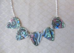 Guitar pick necklace available here. https://www.etsy.com/listing/229621080/abalone-shell-color-guitar-pick-necklace