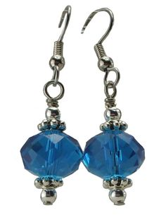 "Simple and elegant these earrings just sparkle. A central faceted rondelle glass bead in Aqua Blue is bracketed by a round 3mm silver plate bead and a pewter bead. It's 1 3/4"" long including the ear w"
