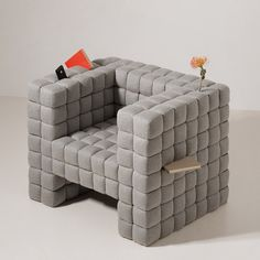 Japanese studio Daisuke Motogi Architecture presented this armchair for holding and hiding things at DesignTide Tokyo 2010. Items can be stored by wedging them into slots between the upholstered cubes that form the seat.