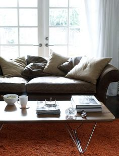 Brown leather sofa - The Hangover Sofa by Highly Sprung in Battersea, London, George Nelson coffee table, orange Ikea shag rug