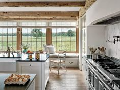 In a Martha's Vineyard home by architect Mark Hutker, the kitchen features black granite counters and rustic wood ceiling beams.