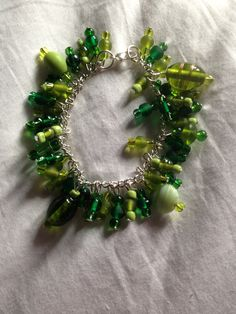 Mixed green opaque and clear glass beaded bulky charm bracelet on silver chain!  Price: £10  Warning: Please keep this bracelet dry at all times! Do not wear it in the shower or continuous water use!
