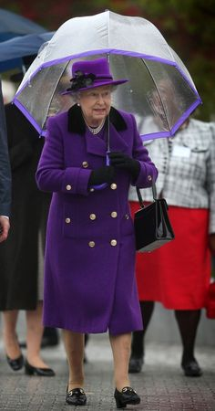 Queen Elizabeth was out and about in the rain. The trim of her umbrella matched her coat and hat. OF COURSE IT DID.