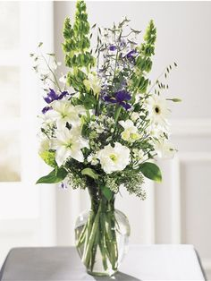 Tall White Flower Arrangements   Blue, green and white flowers arranged in a…