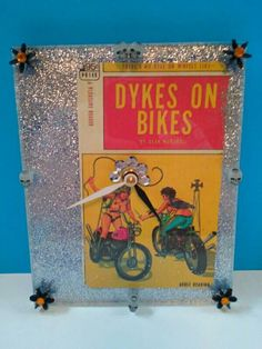 *Celebrate gay/lesbian pride every day with this cool Dykes on Bikes wall clock. A vintage pulp novel called Dykes on Bikes has been sealed under a heavy piece of acrylic and then sealed in the back with glitter adhesive paper. Decorative plastic skulls and colored jewels complete the look. Tell time in dyke style with this unique wall clock. *A standard clock movement has been outfitted with a white hour hand and a black minute hand. Uses one AA battery.(not included) *The measurements ...