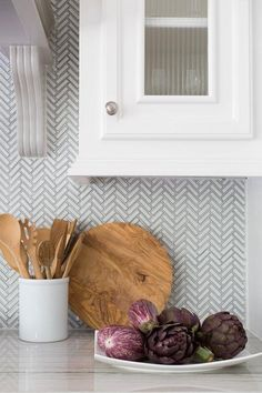 Kitchen featuring white cabinets, quartzite countertops and a gorgeous white and gray herringbone backsplash | Carla Aston
