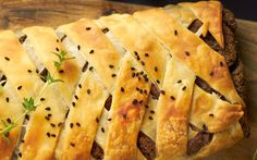 A pastry sheet is filled with a savory and herbed mixture of mushrooms and pecans, topped with a lattice layer of strips, and then baked until golden brown.