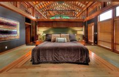 Cavernous master bedroom with cathedral, wood beam ceiling, partial hard wood floor and extensive wood lattice throughout