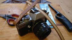 Slim leather women's belt threaded onto steel key rings to attach to camera.