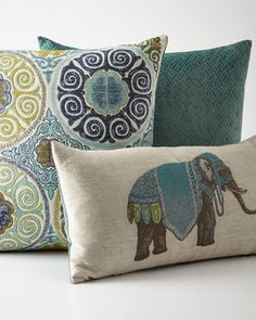 """Azure PillowsHandcrafted. Elephant-print pillow (shown in front) has rayon/cotton/flax front and polyester nylon back; reverses to solid color. 24"""" x 14"""". Medallion-design pillow (shown in middle) has cotton/polyester front and polyester/nylon back; reverses to solid color. 24""""Sq. Maze-design pillow (shown in back) made of polyester; 24""""Sq. All have feather/down fill and hidden zippers. Spot clean."""
