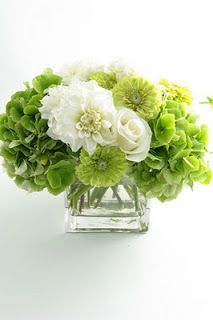 These flower arrangements would be placed down the centre of the table, alternating with candles in rustic lanterns.