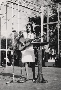 Singer-songwriter Joan Baez performs one of her classic folk ballads at the March for Peace Rally held in Washington, D.C. in 1965. Along with Bob Dylan and the folk trio Peter, Paul, and Mary, Joan Baez was a cultural icon of the 1960's peace and civil rights movements. This Joyce image captures Baez at the height of her musical career and in full command of the large audience that had marched on Washington to protest America's involvement in the Vietnam War.