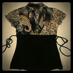 "Paisley and cheetah print top shipping Black and gold top with cheetah and paisley print. Has tie at waist for flattering fit and a ruffled V-neck. Want free shipping? Comment ""free ship"" on any item $10 or more, and I will reduce the price to cover the shipping cost or make offer for $6 less than asking price!  new directions Tops"