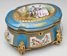 "DESCRIPTION: Sevres style porcelain and ormolu mounted casket. Notched oval shape with handpainted reserves of a couple and putti on a turquoise ground. Ormolu mounts. Tan silk lined and fitted interior housing four glass inkwells with ormolu collars and lids. Lids with handpainted inserts of churches and monuments under glass and retaining original stoppers. 19th century. MEAUREMENTS: 8-1/4"" x 5-3/4"" x 5-1/2"". #antique #vintage #box"