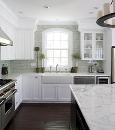 Beautiful white kitchen: marble, dark floors. Open and bright.