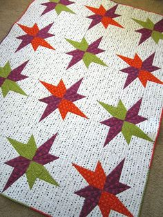 This modern quilt will look stunning in your home. Made using a broken star block this quilt has a element of interest that will catch your eye. This patchwork quilt has colors of orange, purple and g