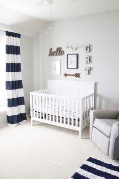 design minimaliste de style marine et boho chic avec rideaux et tapis rayés en bleu marine et blanc et un lit bébé blanc
