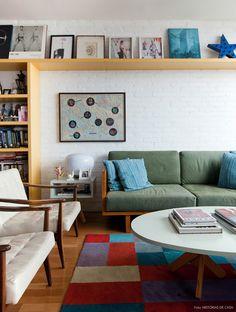 Sala de estar descolada com parede de tijolinho, tapete colorido e móveis de madeira.