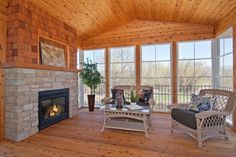3-season porch with tongue in groove knotty pine floors, walls and ceiling. Cedar shakes and natural stone accent fireplace. Creek Hill Custom Homes - Maple Grove, MN