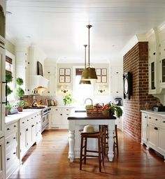 Brighten up the kitchen with white cabinets against the exposed brick!