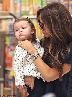 Not the face! Harper looked less than impressed with her mother's choice to touch her cheeks