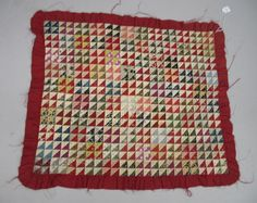 """1000 Triangle pattern. The red, black, purple and blue triangles are 3/4"""". The quilt is bordered by a red ruffle and backed in the same red. Yarn rosettes hold the piece together. Ruffle is frayed. Tear on backing. Minor staining.16 1/2"""" x19"""", Live Auctioneers"""