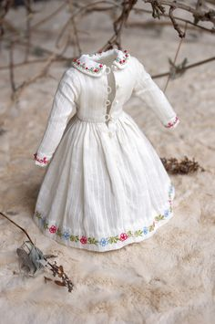 The dress is made of antique white Dimity cotton fabric. All edges were trimmed with small floral embroidery and the front buttonholes band is enhanced with lace and gold metal tiny beads.