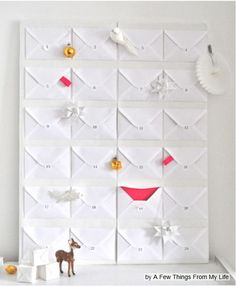 """""""Office envelopes with bright pink lining fill up a poster board. Each envelope is numbered and filled with quirky holiday treats. """" from houzz  http://www.houzz.com/ideabooks/966872/list/30-Beautifully-Inventive-DIY-Christmas-Decorations"""