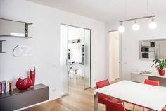 Un intérieur magnifique avec ces touches de couleur rouges dans la pièce. La porte verre et aluminium s'harmonise avec la décoration intérieure pour une ambiance chic et reposante.