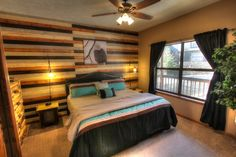 Sasquatch Ridge Pigeon Forge vacation rental cabin - main level Eagle bedroom. This room has a king bed with memory foam mattress, wood accent wall, handmade side tables, mason jar lamps, log dresser, television and ceiling fan.