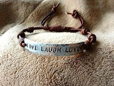 I hand stamped the words Live Laugh Love onto a non tarnish hypoallergenic silver plate and hammered the edges of it to give it a neat textured