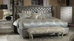 4281 SILVER GLAM BED  The glamor created by the contours of the curved headboard and wings of this bed is not easily matched. However, it is greatly complemented by the elegant, dark silver, tufted upholstery. While beautiful chrome nailheads line the headboard, the white buttons in the tufts add brightness and variety to this exquisite bed.