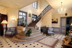 This entrance hall to a 19th-Century castle outside Rouen has a marble staircase, wrought-iron railings, marble tile floors and walls painted to resemble stone.  NYTimes.com