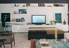 Versátil, o móvel deste home theater também oferece uma bancada para o computador, além de prateleiras e gavetões para CDs e DVDs. Feito de madeira laqueada, este painel de 7,33 x 2,30 m de altura tem marcenaria da Madeirart. À frente dele, pufes da Jocal.