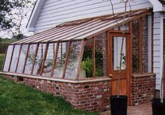 This lean-to greenhouse has a brick base for thermal mass and is partially burie. This lean-to gre Lean To Greenhouse, Greenhouse Effect, Greenhouse Growing, Greenhouse Plans, Backyard Greenhouse, Greenhouse Wedding, Greenhouse Attached To House, Pallet Greenhouse, Homemade Greenhouse