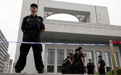 China may drop 9 crimes from death penalty list offenses. Photograph: Police officers stand guard in front of the Hefei City Intermediate People's Court in China's Anhui Province.