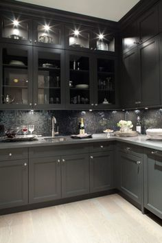 GRAY KITCHEN. MY DREAM <3 Gorgeous black kitchen design with oak wood floors, black shaker kitchen cabinets, gray quartz countertops and glass-front black glass tiles backsplash. the lighting makes this too dark kitchen amazingly inviting