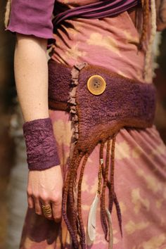 This is an AMAZING piece of art !!!  I made this belt/pocket in soft merino wool and Ive added some textures into it with silk fibers and beautiful purple lace. There is so many details into this unique creation. A beautiful spiral symbol is adorning the back and inside pocket . A symbol that activate movement !  It is felted thin and lightweight , yet strong and durable it has been felted in one piece . It comes with a matching cuff in purple .  There is a spacious pocket hanging on the...