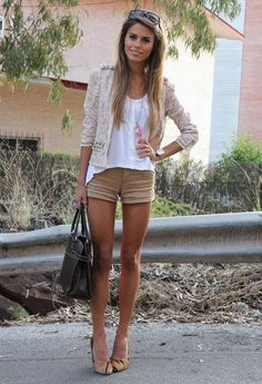 This is an example of spring clothes. The tan skin, light hair and white shrug show warmth and the tan rolled up shorts and tan pumps also show a warm season. The pink necklace also adds flair.