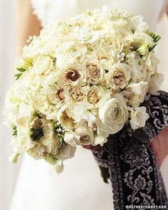 An armful of white flowers, including Majolica spray roses, lily of the valley, Ranunculus, freesia, Lisianthus, and sweet peas, is bound with a black-and-white sash tied in a grand bow.