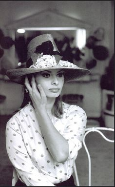 1964 Sophia Loren trying on a hat from Givenchy
