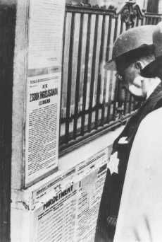 A Jewish man wearing a yellow star reads newly posted antisemitic regulations in Budapest. Hungary, 1944.