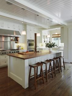 butcher-block island counter, white cabinets to the ceiling, beadboard ceiling, matchstick blinds on kitchen's only window