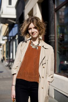 style in the streets. leaf necklace. burnt sienna top. black bottom. trench coat