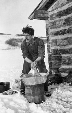 Rancher Washing Socks....George Pocaterra doing laundry outside his cabin, Longview, Alberta. [ca. 1907]