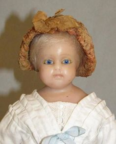 OVERVIEW: This is a charming English Poured Wax Doll. Her wax shoulder-head, arms and legs are in excellent condition. She is wearing 5 layers of antique/original clothing and she retains her original
