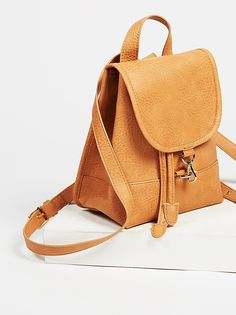 Essential faux leather backpack with a chic structured shape. Drawstring and lobster clasp closures. Adjustable straps and top handle for easy carrying. Inside pocket with zipper closure.