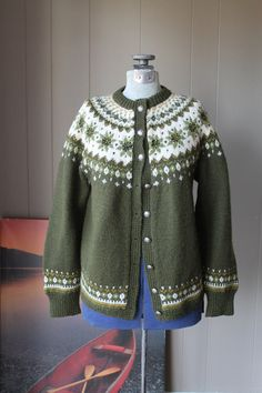 This amazing non-itchy and moth proof wool sweater has been hand knit in Norway. It is soft and gorgeous wool and a beautiful moss green. It measures 19 inches from underarm to underarm in the front and 23 inches down from the collar to the hem. The sleeves are 27 and a half inches from the collar seam to the end of the sleeve. The pattern is just so beautiful. This is not a heavy sweater and could easily be worn in the spring especially as the colors are so springlike. It appears to have…