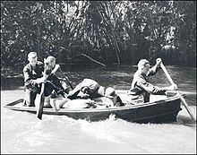 In 1942, three members of the 32nd Infantry Division move supplies by boat on the Girau River, Buna, New Guinea. With no roads through the jungle, the only way to keep the troops furnished with the food, ammunition and other goods necessary to operate against the Japanese was via water and airborne supply.